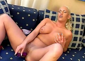 Blonde cougar with a fabulous body playing with her pussy on her sofa