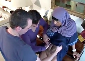 Sexy Arab slut in a hijab blows two guys at the same time